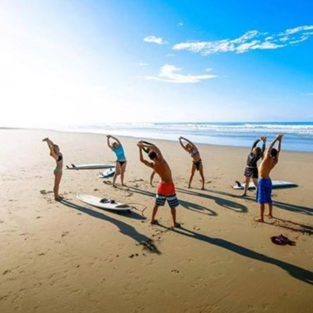 Stretching before surf lessons, Pranamar Oceanfront Villas. Ohoto credit pranamarvillas.